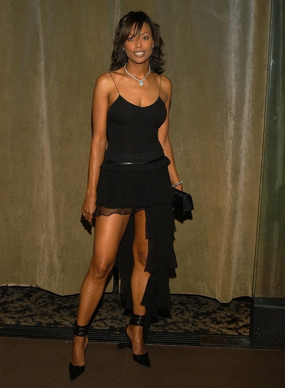 Aisha Tyler in black skirt showing off her legs